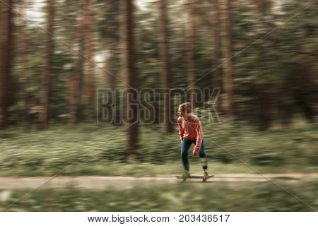 Young Man In Stylish Clothes Skates On A Skateboard At A Speed In The Park