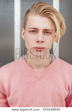 Portrait Of A Handsome Young Man With A Blond Hairstyle In A Pink Sweater Near The Wall