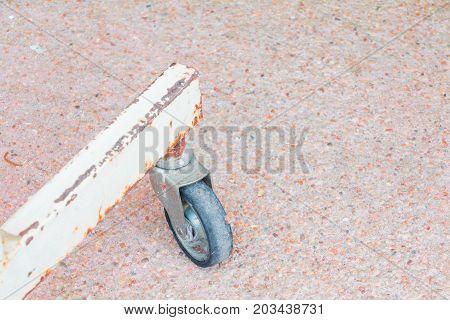 black rubber wheel rusty old small metal transportation metal on floor sandstone