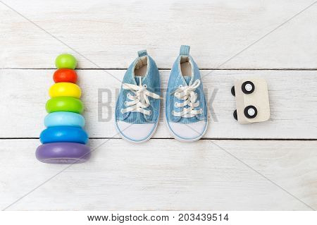 blue baby sneakers and wooden toys on a wooden background