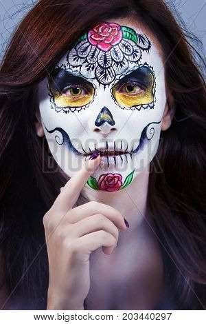 Portrait of a beautiful young woman in a Halloween style. Aquagrim - the skull