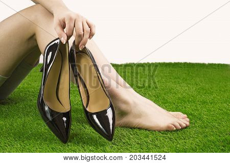 Bare Feet On Green Grass. The Girl Takes Off Her Shoes And Holds Them. White Background