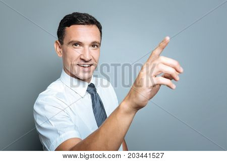Positive mood. Delighted nice good looking man holding his hand up and smiling while looking at you