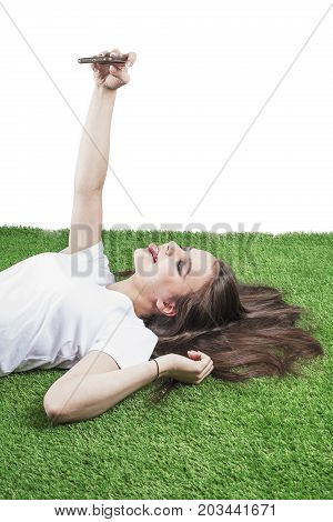 Happy Beautiful Lady Lies On The Grass Using A Smart Phone And Shows Tongue. Beautiful Young Woman W