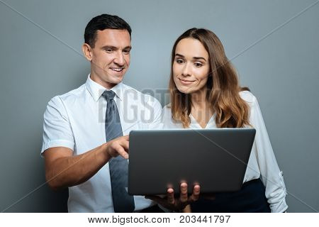 Pleasant cooperation. Nice pleasant cheerful man standing with his colleague and showing her a picture while holding a laptop