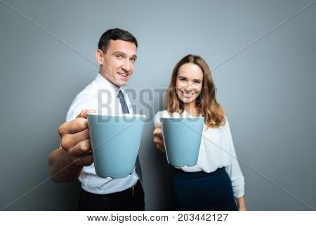 Would you like some tea. Selective focus of cups with tea being given to you by positive cheerful friendly man and woman