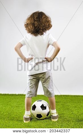 Youth Soccer Player Standing Holding His Hands In The Sides On The Green Grass. Rear View