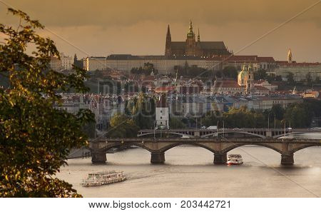 Fall scenery of the Prague Castle - Saint Vitus cathedral Saint Nicolas Church and bridges over Vltava river and boats. Yellow autumn cityscape.