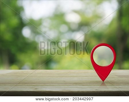 Map pin location button on wooden table over blur green tree in park Map pointer navigation concept