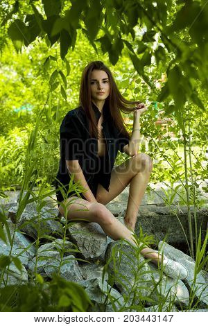 slender sexy girl sitting on rocks and looks at the camera