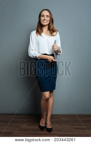 Professional ceo. Cheerful positive smart businesswoman holding her laptop and looking at you while working as a professional ceo