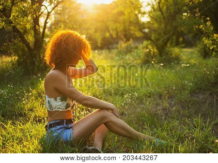 Beautiful young redhair woman sitting in a park in the sunset.