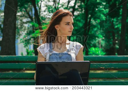 Portrait of charming young brunette on a bench with a black laptop