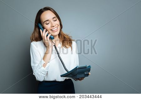 Corded telephones. Pleasant delighted pretty woman holding a corded telephone and putting receiver to her ear while making a call