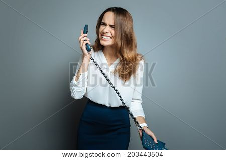 Unpleasant conversation. Nice emotional pleasant woman holding a phone receiver and feeling unhappy while having unpleasant conversation