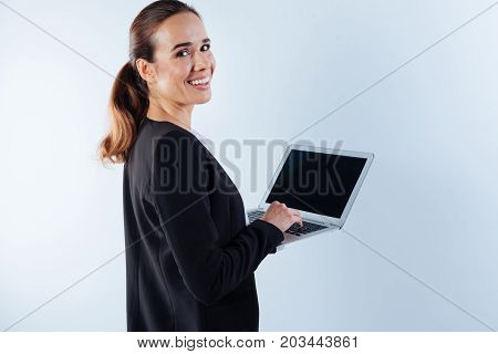 Compact size. Nice joyful positive businesswoman holding a netbook and turning to you while using it for work