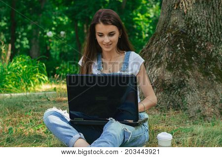 young smiling lady sitting with big black laptop in the Park on the grass