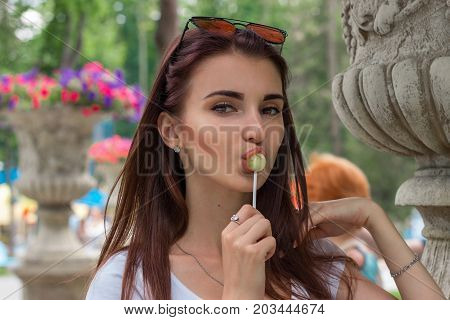 a close-up portrait of young sexual woman with lollipop in her mouth