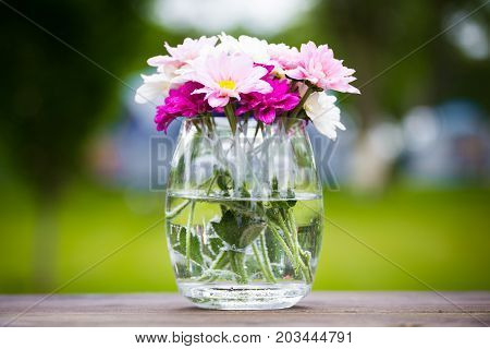 Decorative posy of fresh pink summer flowers in a glass vase on an outdoor wooden table viewed close up on the side