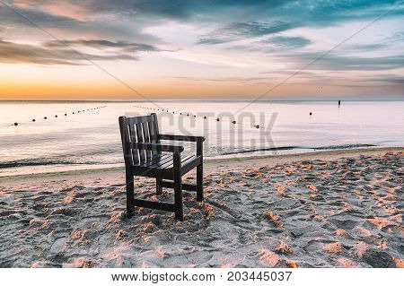 Chair left on the beach at sunrise with beautiful clouds
