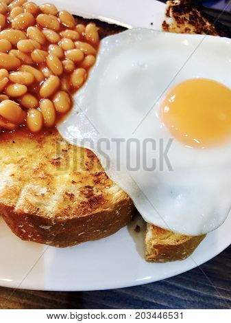 Fried egg and baked beans on thick white sliced toast