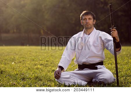 The expert of martial arts is sitting in white kimono with sword on grass outdoor.