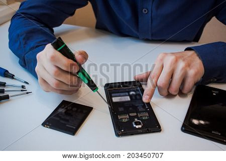 close up picture of hands and broken cellphone, men repair smartphone
