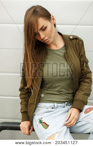 Beautiful young woman with freckles in street style in a jacket and a T-shirt with jeans near a metal wall