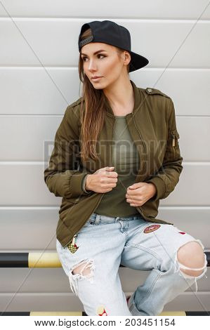 Beautiful Stylish Woman With Freckles In A Baseball Cap In A Fashionable Green Jacket With Torn Jean