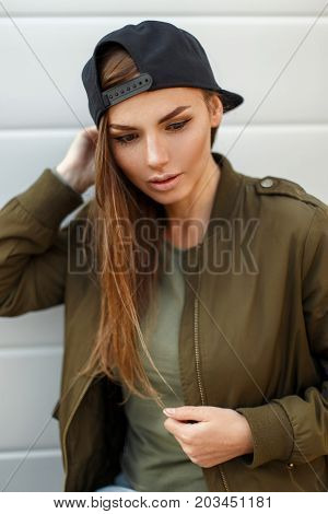 Portrait Of A Beautiful Young Woman In A Black Baseball Cap In A Trendy Green Jacket Looks Down