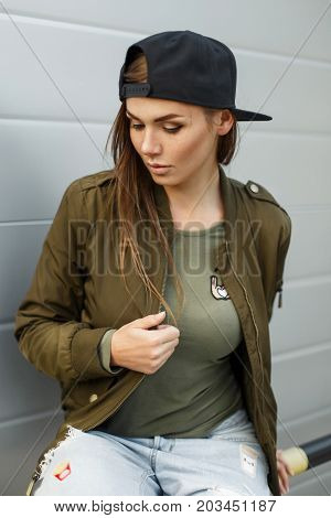 Beautiful Young Woman Model With Freckles In A Baseball Cap And Fashionable Green Military Jacket Ne