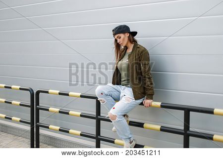 Beautiful Young Fashionable Woman In A Baseball Cap In Street Style Clothes Sitting Near A Wall