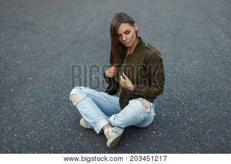 Beautiful Young Woman With Freckles In A Fashionable Military Jacket Sits On The Asphalt