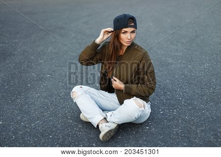 Vogue Model Woman In A Baseball Cap In A Green Stylish Jacket And Torn Jeans Sits On The Asphalt