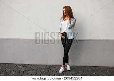 Beautiful Young Woman In Casual Stylish Clothes In A Blue Shirt In Black Pants And White Shoes Near
