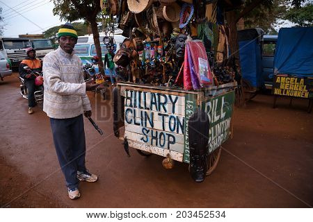 ARUSHA, TANZANIYA - CIRCA 2015: SMALL OUTDOOR GIFT SHOP MENTIONING POLITICIANS AND A STREET VENDOR