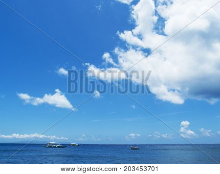 Sea water landscape with blue sky and ripples. Seashore view with white boats. Blue sky with white cloud. Summer weather on tropical island. Exotic seaside travel destination place. Seaside banner