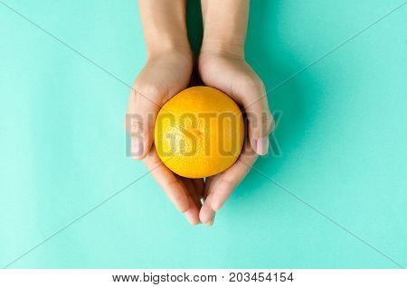 Navel orange fruit hold by hand on green background,healthy eating