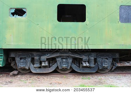 Side view of an old green train passenger car with a broken window, detailing the wheel and undercarriage configuration, horizontal view