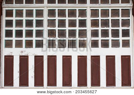 Multiple panes of glass in wood window frames with weathered paint panels, horizontal view