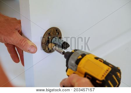 Installation Of Door Lock Using A Screwdriver To. Carpenter At Lock Installation With Electric Drill