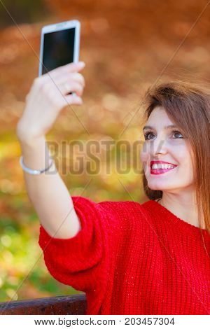 Technology and fun concept. Enjoyable attractive girl playing with mobilephone. Cheerful gorgeous woman smiling taking selfie photo in seasonal autumnal park forest.