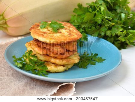 fried fritters of zucchini with parsley on white background