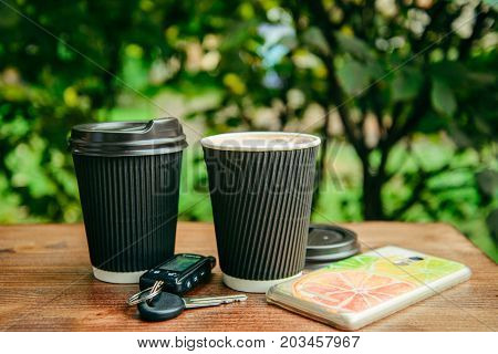 two cups of coffee on the wooden table with car keys