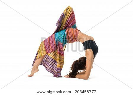 Slim girl striped sarong wraped over her body doing yoga back bending gracefully indoors isolated on white