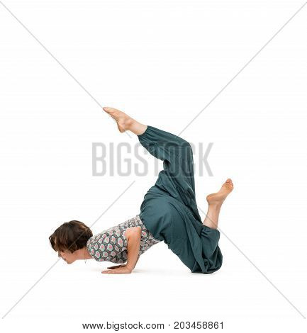 Young woman wearing top and wide trousers practising her yoga routine making hand stand isolated on white