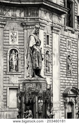 Old statue of Charles IV and St. Francis of Assissi church Prague Czech republic. Black and white photo.