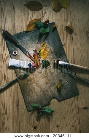 Wooden palette with oil paints yellow red, brushes and palette knife over wooden floor. With autumn decoration yellow leaves and red berries. Top view with space. Art concept. Atmospheric day light