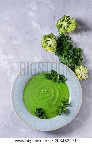 Vegetarian broccoli cream soup served in blue plate with fresh parsley and broccoli over gray concrete background. Top view with copy space. Healthy eating.