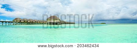 Panoramic landscape of Maldives beach with overwater bungalow